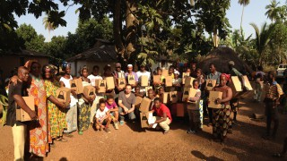 """handing out the lamps to the villagers of Domingya, Guinea, with the non-profit-organisation  """"les petits anges de guinée""""."""